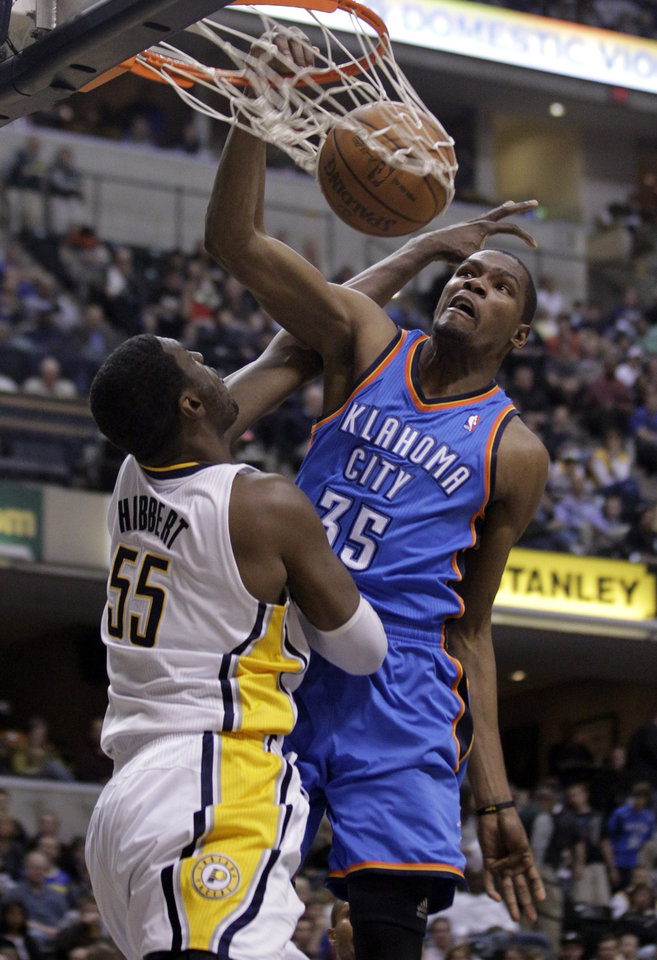 Photo - Oklahoma City Thunder forward Kevin Durant, right, dunks over Indiana Pacers center Roy Hibbert in the first half of an NBA basketball game in Indianapolis, Friday, April 6, 2012. (AP Photo/Michael Conroy) ORG XMIT: NAF101