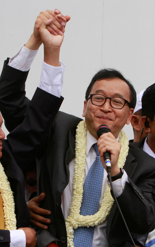 Photo - Sam Rainsy, president of Cambodia National Rescue Party (CNRP) greets his supporters on his arrival at Phnom Penh International Airport, in Phnom Penh, Cambodia, Friday, July 19, 2013. Thousands of cheering supporters greeted Cambodian opposition leader Sam Rainsy as he returned from self-imposed exile Friday to spearhead his party's election campaign against well-entrenched Prime Minister Hun Sen. (AP Photo/Heng Sinith)
