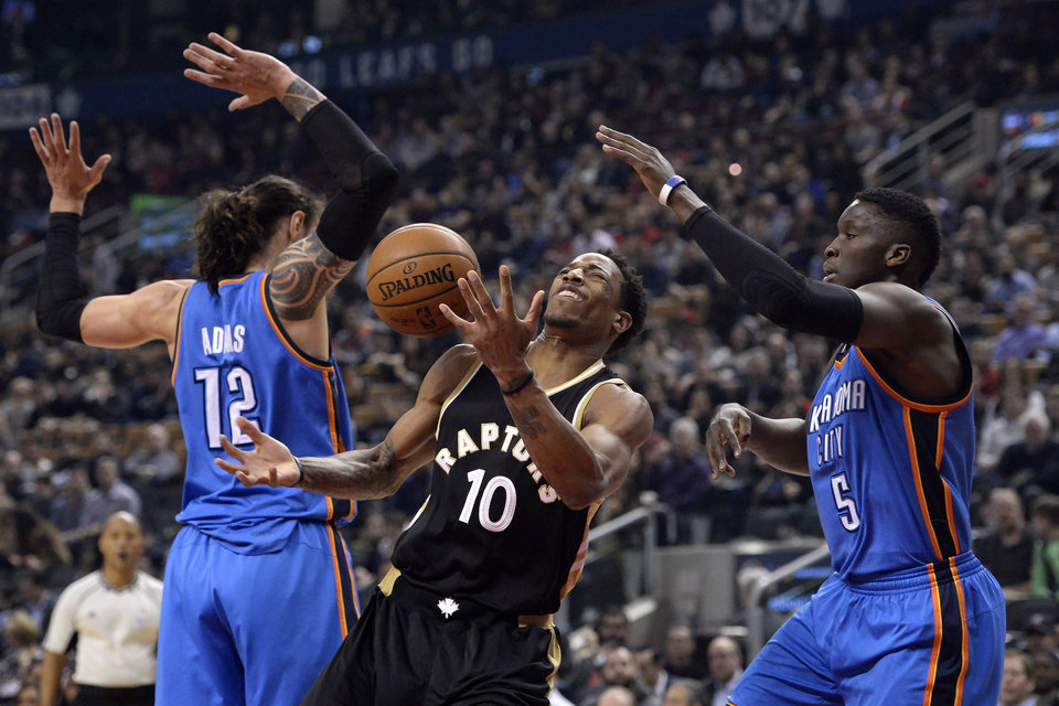 Photo - Toronto Raptors guard DeMar DeRozan (10) gets blocked by Oklahoma City Thunder center Steven Adams (12) and guard Victor Oladipo (5) during the first half of an NBA basketball game Thursday, March 16, 2017, in Toronto. (Nathan Denette/The Canadian Press via AP)