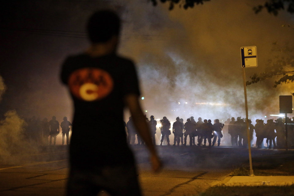 Photo - A man watches as police walk through a cloud of smoke during a clash with protesters Wednesday, Aug. 13, 2014, in Ferguson, Mo. Protests in the St. Louis suburb rocked by racial unrest since a white police officer shot an unarmed black teenager to death turned violent Wednesday night, with people lobbing Molotov cocktails at police who responded with smoke bombs and tear gas to disperse the crowd. (AP Photo/Jeff Roberson)