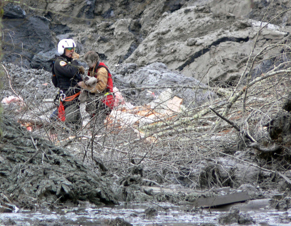 In this photo, published Sunday, March 30, 2014, by the Seattle Times, Randy Fay, a volunteer rescue technician with Snohomish County's SnoHawk 10 rescue helicopter, helps Jetty Dooper, from the Netherlands, after a mudslide struck near Oso, Wash., on Saturday, March 22, 2014. Dooper, while visiting her friend Robin Youngblood who lived in the area, was caught in the slide when a wave of mud crashed into Youngblood's house. (AP Photo/Larry Taylor)