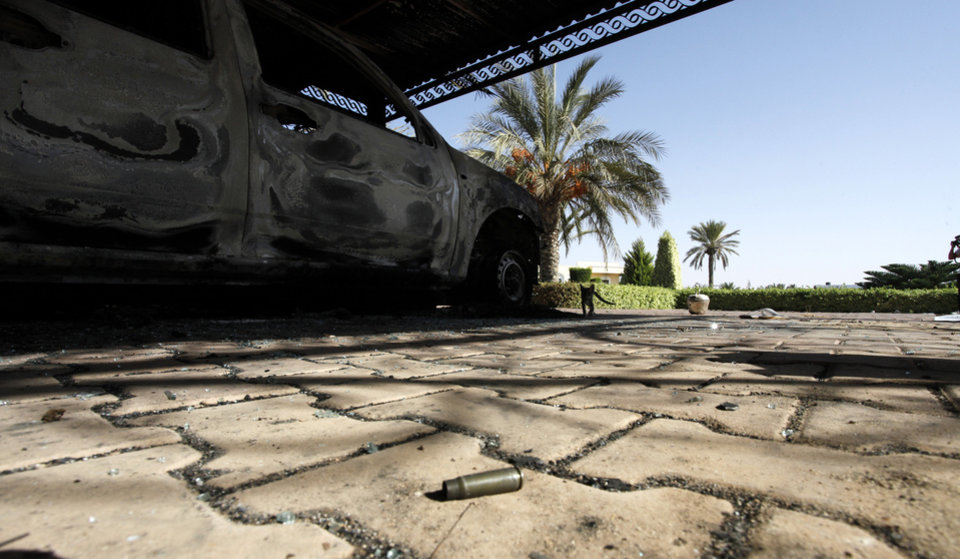 Photo -   FILE - In this Thursday, Sept. 13, 2012 file photo, an empty bullet casing lies on the ground near one of the burned cars at the U.S. Consulate after an attack that killed four Americans, including Ambassador Chris Stevens on the night of Tuesday, Sept. 11, 2012, in Benghazi, Libya. Witness accounts gathered by The Associated Press give a from-the-ground perspective for the sharply partisan debate in the U.S. over the deadly incident. They corroborate the conclusion largely reached by American officials that it was a planned militant assault. But they also suggest the militants may have used a film controversy as a cover for the attack. (AP Photo/Mohammad Hannon)