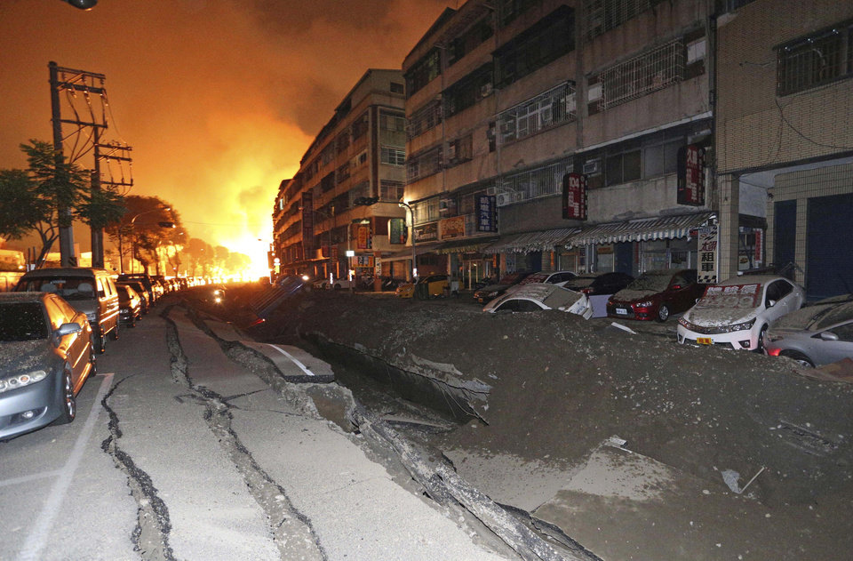 Photo - Tossed vehicles line an destroyed street as flames continue to burn from multiple explosions from an underground gas leak in Kaohsiung, Taiwan, early Friday, Aug. 1, 2014.  A massive gas leakage early Friday caused five explosions that killed several people and injured over 200 in the southern Taiwan port city of Kaohsiung. (AP Photo)  TAIWAN OUT