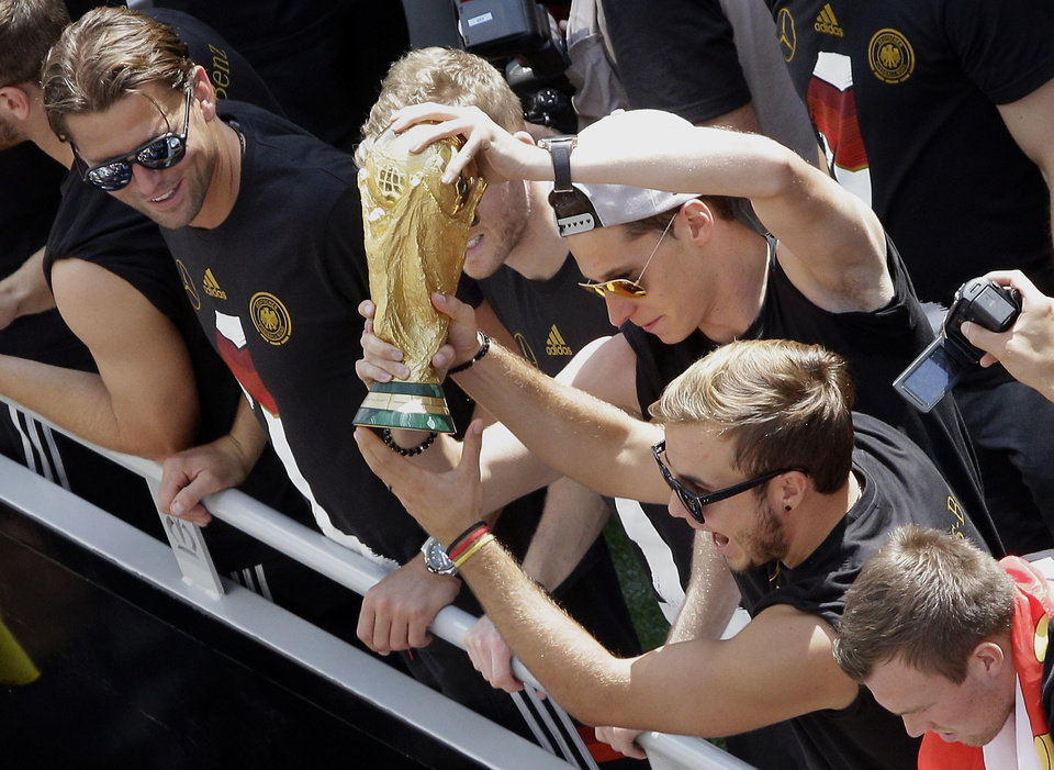 """Photo - German soccer players Mario Goetze, right, and Julian Draxler , center, hold the trophy while goalie Roman Weidenfeller , left, looks on,  after the arrival of the German national soccer squad  in Berlin Tuesday, July 15, 2014. Germany's World Cup-winning team has returned home  from Brazil to celebrate the country's fourth title with huge crowds of fans. The team's Boeing 747 touched down at Berlin's Tegel airport midmorning Tuesday after flying a lap of honor over the """"fan mile"""" in front of the landmark Brandenburg Gate.   (AP Photo/Michael Sohn)"""