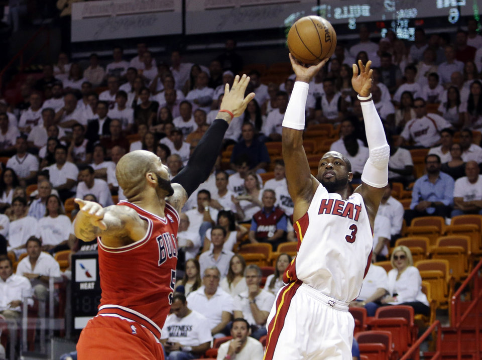 Photo - Miami Heat guard Dwyane Wade (3) shoots against Chicago Bulls forward Carlos Boozer (5) during the first half of Game 2 of their NBA basketball playoff series in the Eastern Conference semifinals, Wednesday, May 8, 2013, in Miami. (AP Photo/Lynne Sladky)