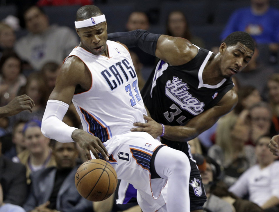 Photo - Charlotte Bobcats' Brendan Haywood (33) and Sacramento Kings' Jason Thompson (34) battle for a rebound during the first half of an NBA basketball game in Charlotte, N.C., Saturday, Jan. 19, 2013. (AP Photo/Chuck Burton)