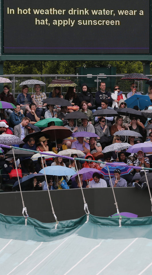 Photo - Spectators shelter under umbrellas as an  information board warns spectators to take care in the sunshine, as  rain delays the start of matches at the All England Lawn Tennis Championships in Wimbledon, London, Friday, June 27, 2014. (AP Photo/Ben Curtis)