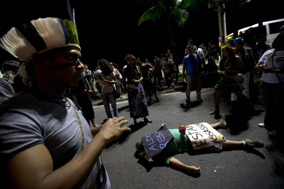Photo - A protester lies on a street covered by posters that read in Portuguese;