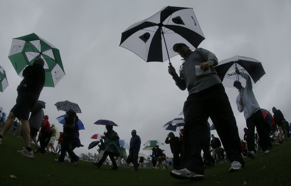 Photo - Spectators walk off the course after play was suspended because of severe weather during the first day of practice for the Masters golf tournament Monday, April 7, 2014, in Augusta, Ga. (AP Photo/Charlie Riedel)