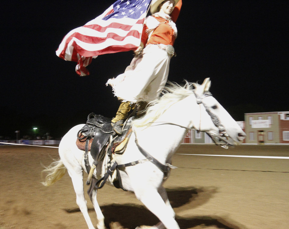 Trick rider Wendy Ratchford stands on horseback as she rides in front of the crowd waving an American flag during  the Pawnee Bill Wild West Show in Pawnee, Oklahoma on Saturday,  June 23, 2012.  Photo by Jim Beckel, The Oklahoman
