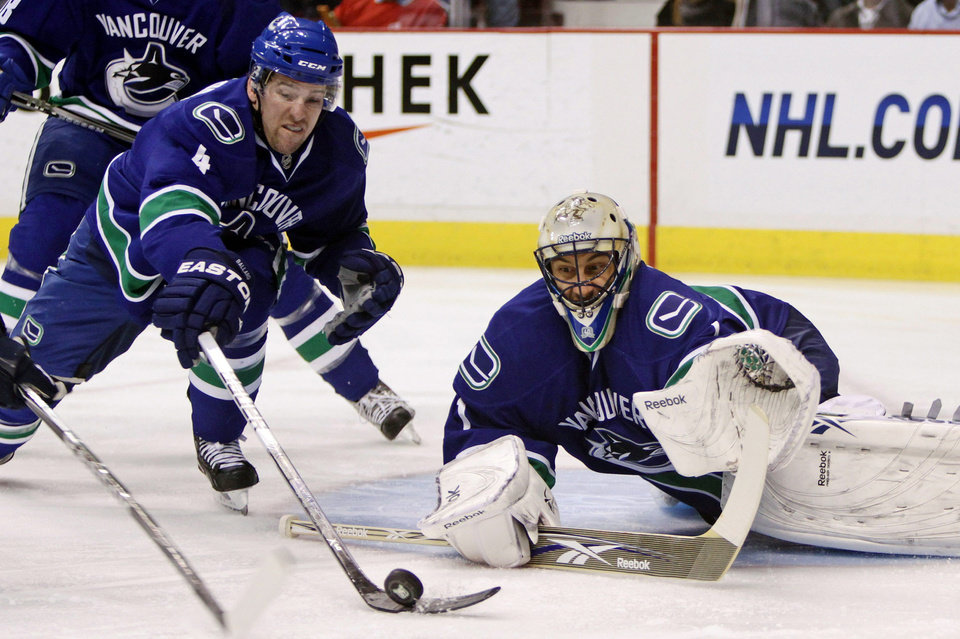 Vancouver Canucks' Keith Ballard, left, reaches for the puck as goalie Roberto Luongo follows the play during the first period of an NHL hockey game against the Nashville Predators, in Vancouver, in Vancouver, British Columbia, on Wednesday, Jan. 26, 2011. (AP Photo/The Canadian Press, Darryl Dyck)
