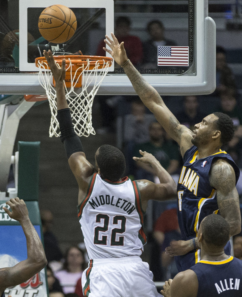 Photo - Milwaukee Bucks' Khris Middleton (22) shoots the ball over Indiana Pacers' Rasual Butler during the second half of an NBA basketball game on Wednesday, April 9, 2014, in Milwaukee. (AP Photo/Tom Lynn)
