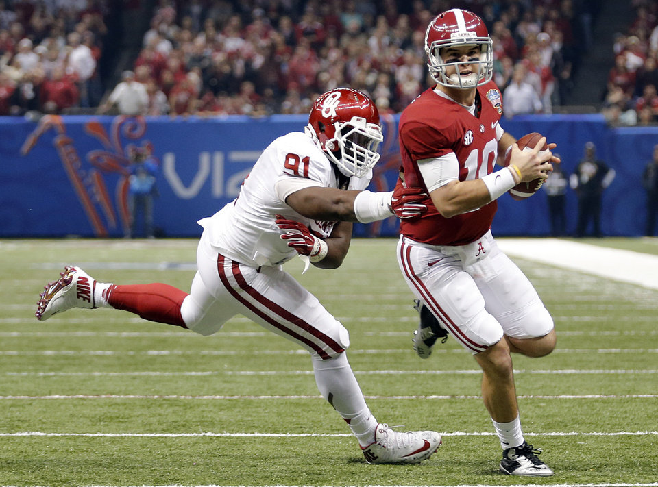 Photo - Alabama's AJ McCarron (10) runs past Oklahoma's Charles Tapper (91) during the NCAA football BCS Sugar Bowl game between the University of Oklahoma Sooners (OU) and the University of Alabama Crimson Tide (UA) at the Superdome in New Orleans, La., Thursday, Jan. 2, 2014.  .Photo by Chris Landsberger, The Oklahoman