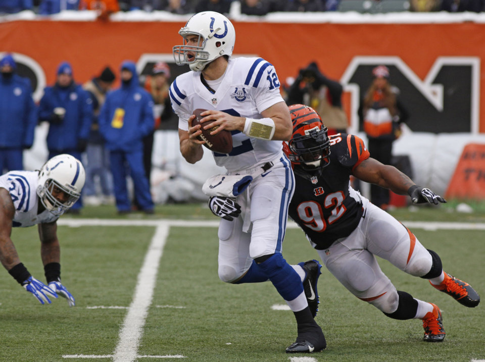 Photo - Indianapolis Colts quarterback Andrew Luck (12) is pursued by Cincinnati Bengals outside linebacker James Harrison (92) in the first half of an NFL football game, Sunday, Dec. 8, 2013, in Cincinnati. (AP Photo/David Kohl)