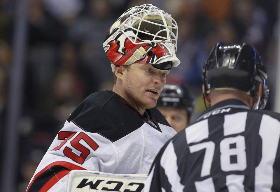 Photo - New Jersey Devils goalie Cory Schneider, left, confers with linesman Brian Mach during a timeout against the Colorado Avalanche in the second period of an NHL hockey game in Denver, Thursday, Jan. 16, 2014. (AP Photo/David Zalubowski)