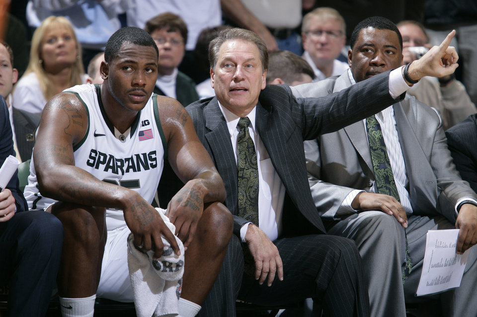 Photo - Michigan State coach Tom Izzo, center, sits next to Derrick Nix, left, on the bench during the second half of an NCAA college basketball game against Texas, Saturday, Dec. 22, 2012, in East Lansing, Mich. At right is associate head coach Dwayne Stephens. Michigan State won 67-56. (AP Photo/Al Goldis)