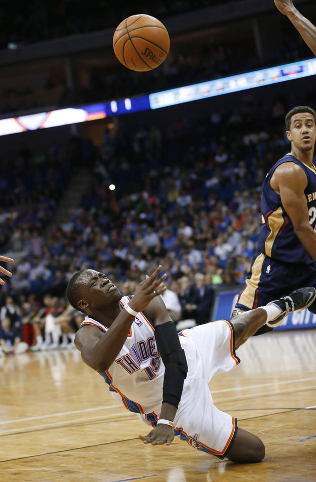 Photo - Oklahoma City Thunder guard Reggie Jackson (15) shoots against the New Orleans Pelicans while falling to the floor in the fourth quarter of an NBA basketball preseason game in Tulsa, Okla., Thursday, Oct. 17, 2013. New Orleans guard Brian Roberts is at right. The Pelicans won 105-102. (AP Photo/Sue Ogrocki) ORG XMIT: OKSO120