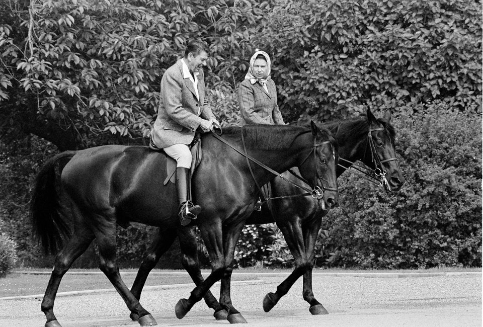 FILE - In this June 8, 1982 file photo, U.S. President Ronald Reagan, on Centennial, and Britain\'s Queen Elizabeth II, on Burmese, go horseback riding on the grounds of Windsor Castle, England. It is not often that the president of the United States needs to seek fashion advice. But when Ronald Reagan was getting ready for a visit to England as a guest of Queen Elizabeth II in June 1982, his people had an important question for the Brits: Just what does one wear to go riding with the queen in the magnificent horse country surrounding Windsor Castle? The answer: Something smart, but casual, of course. Riding boots, breeches and a turtleneck sweater would do fine _ no need for formal riding attire. The fashion inquiry is but one tidbit contained in nearly 500 pages of formerly Confidential documents relating to the Reagan visit being made public Friday, Dec. 28, 2012 by Britain's National Archives. (AP Photo/Bob Daugherty, File)