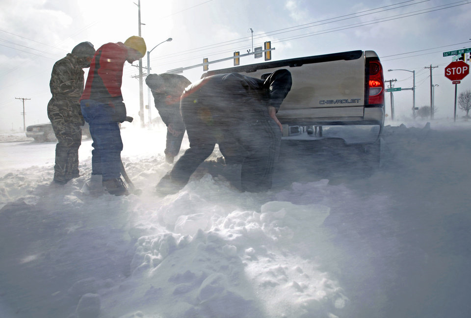 Photo - Eric Thurston (right) connects a tow rope to his four-wheel-drive pickup as good-samaritans Rod Thornton, his son Jake, and Chad Williams prepare to pull him from a snow drift after an epic winter storm on Tuesday, February 1, 2011, in Norman, Okla.  Thurston who spent the day helping other stranded motorists said this the first time he has ever been stuck in the snow in either his native Canada or in Oklahoma.  Photo by Steve Sisney, The Oklahoman