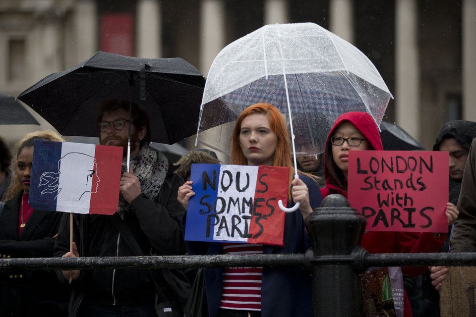Photo - People holding placards listen to speakers as they take part in a vigil for victims of the deadly attacks in Paris, in Trafalgar Square, London, Saturday, Nov. 14, 2015. French President Francois Hollande said more than 120 people died Friday night in shootings at Paris cafes, suicide bombings near France's national stadium and a hostage-taking slaughter inside a concert hall. (AP Photo/Matt Dunham)