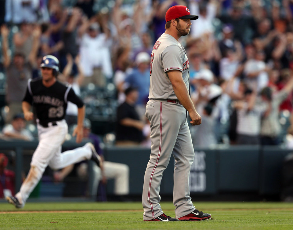 Photo - Cincinnati Reds relief pitcher J.J. Hoover, front, reacts after giving up a three-run walkoff home run to Colorado Rockies' Drew Stubbs in the ninth inning of the Rockies' 10-9 victory in a baseball game in Denver, Sunday, Aug. 17, 2014. (AP Photo/David Zalubowski)