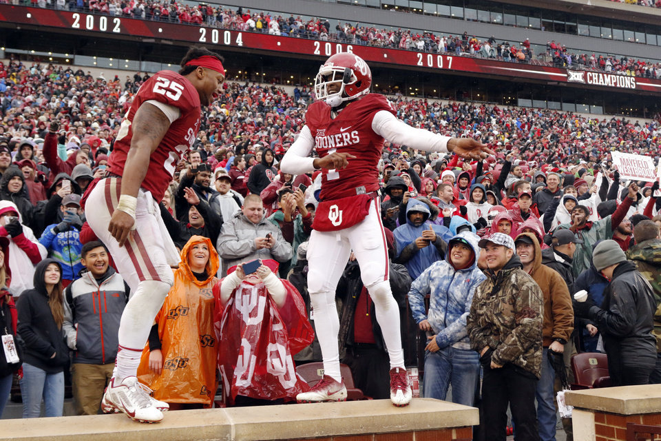 Photo - Oklahoma's Joe Mixon (25) and Jarvis Baxter (1) dance in the stands following the Bedlam college football game between the Oklahoma Sooners (OU) and the Oklahoma State Cowboys (OSU) at Gaylord Family - Oklahoma Memorial Stadium in Norman, Okla., Saturday, Dec. 3, 2016. Photo by Steve Sisney, The Oklahoman