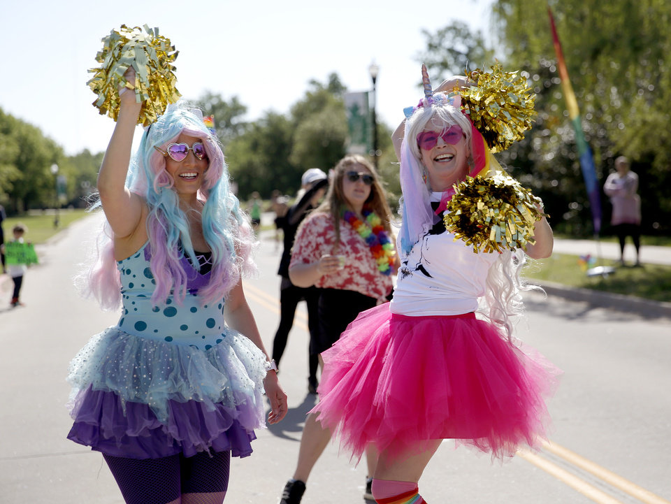 Photo - Juliana Marin, left, and Nicole Poole cheer on runners at Glitter on Grand during Oklahoma City Memorial Marathon in Oklahoma City, Sunday, April 28, 2019. [Sarah Phipps/The Oklahoman]