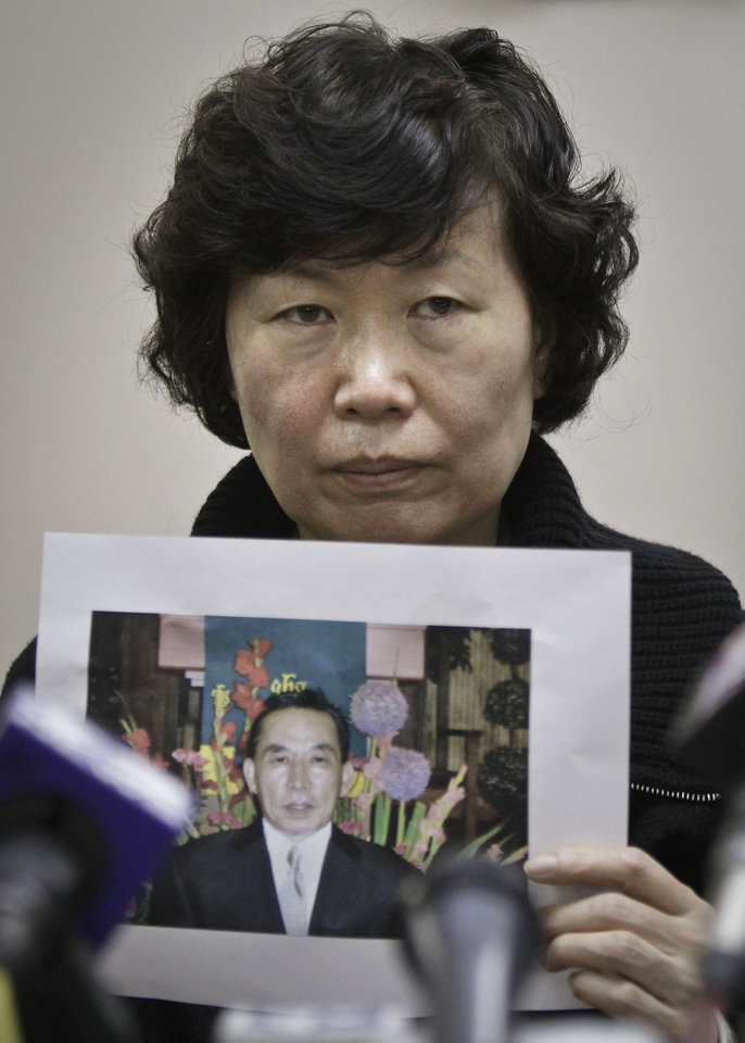Photo - Serim Han holds a picture of her husband Ki-Suck Han during a news conference on Wednesday, Dec. 5, 2012 in New York. A homeless man was arrested Wednesday in the death of Ki-Suck Han, who was pushed onto the tracks and photographed just before a train struck him.  (AP Photo/Bebeto Matthews)