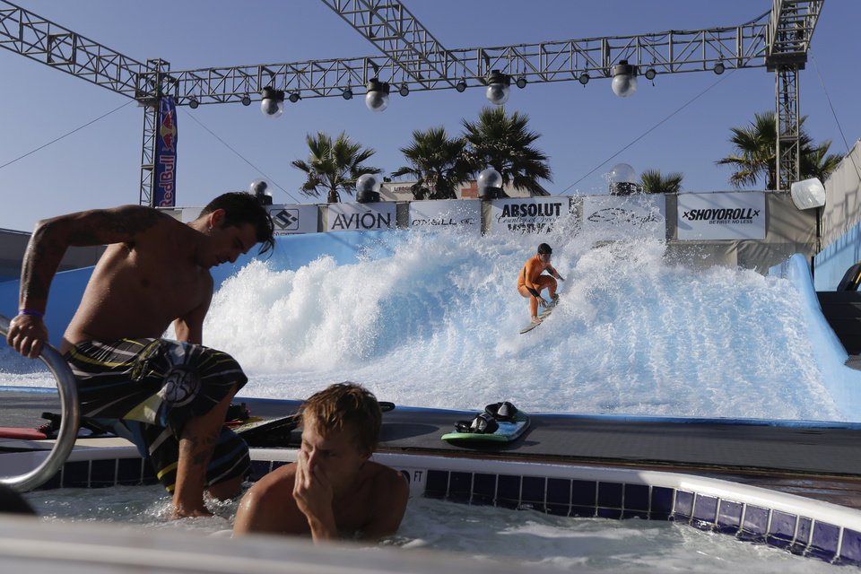Professional surfer Gabriel Medina, of Brazil, back, rides the machine-made wave at Wavehouse San Diego, as two men sit in a jacuzzi Wednesday, Sept. 18, 2013, in San Diego. Surf parks - massive pools with repeating, artificial waves - are the latest buzzword in the surf community, as everyone from top athletes to retailers look for ways to expand the sport, boost surf-related sales and create a standardized way to train that could ultimately help surfing earn an Olympic pedigree. (AP Photo/Gregory Bull)