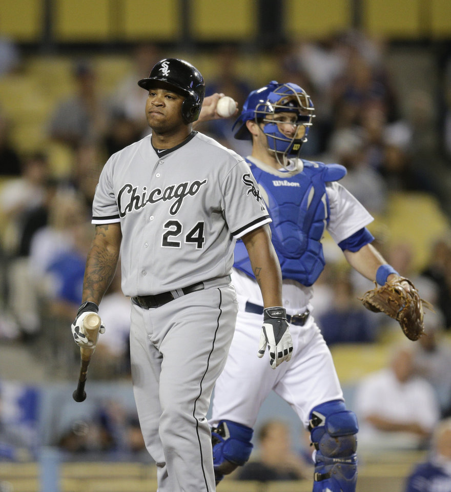 Photo - Chicago White Sox's Dayan Viciedo, left, walks off the field after striking out as Los Angeles Dodgers catcher Drew Butera throws the ball to relief pitcher Kenley Jansen during the ninth inning of a baseball game on Monday, June 2, 2014, in Los Angeles. The Dodgers won 5-2. (AP Photo/Jae C. Hong)