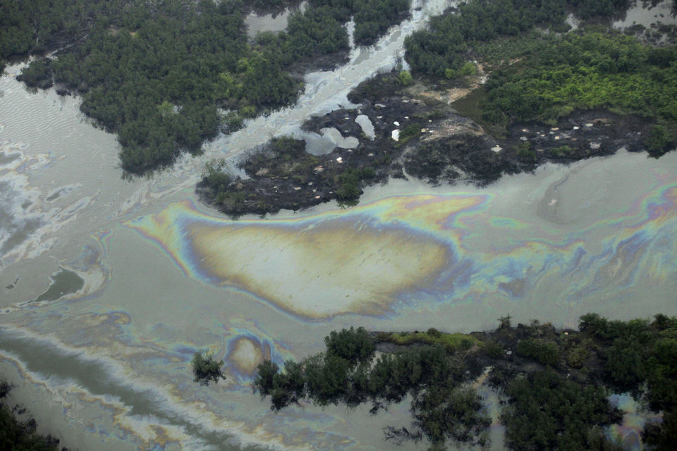 Photo - FILE - In this March 24, 2011 file photo, oil is seen on the creek water's surface near an illegal oil refinery in Ogoniland, outside Port Harcourt. Little action has been taken to clean up pollution caused by oil production in Nigeria's Niger Delta region, either by the government or Shell Oil, Amnesty International and other groups charged Monday. Aug. 4, 2014. Oil production has contaminated the drinking water of at least 10 communities in the Ogoniland area but neither the Nigerian government nor Royal Dutch Shell's Nigeria subsidiary have taken effective measures to restore the fouled environment, said the new report by Amnesty International, Friends of The Earth Europe, Center for Environment, Human Rights and Development, Environmental Rights Action, and Platform.  (AP Photo/Sunday Alamba, File)