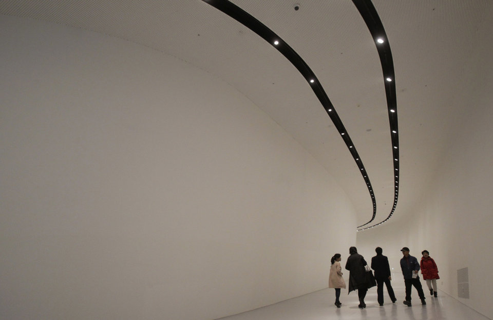 Photo - Visitors walk inside Dongdaemun Design Plaza in Seoul, South Korea, Friday, March 21, 2014. The $450 million building funded by Seoul citizen's tax money finally opened to public on Friday after years of debates about transforming a historic area with an ultra-modern architecture. (AP Photo/Ahn Young-joon)