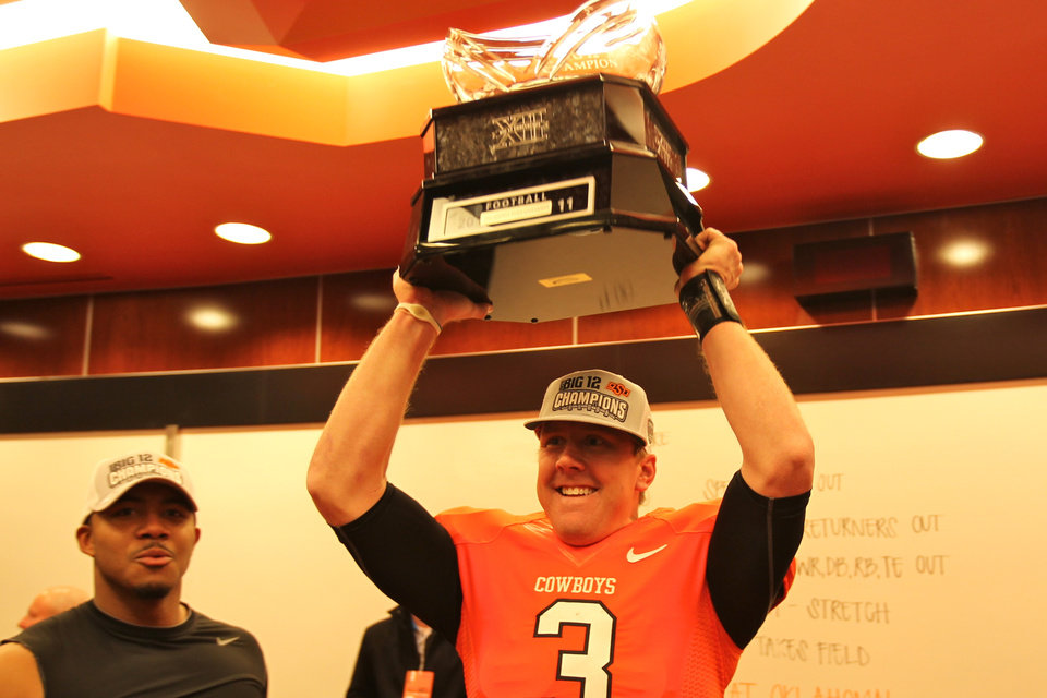 Photo - Oklahoma State quarterback Brandon Weeden celebrates with the Big 12 Championship trophy. PHOTO COURTESY OSU SPORTS INFORMATION