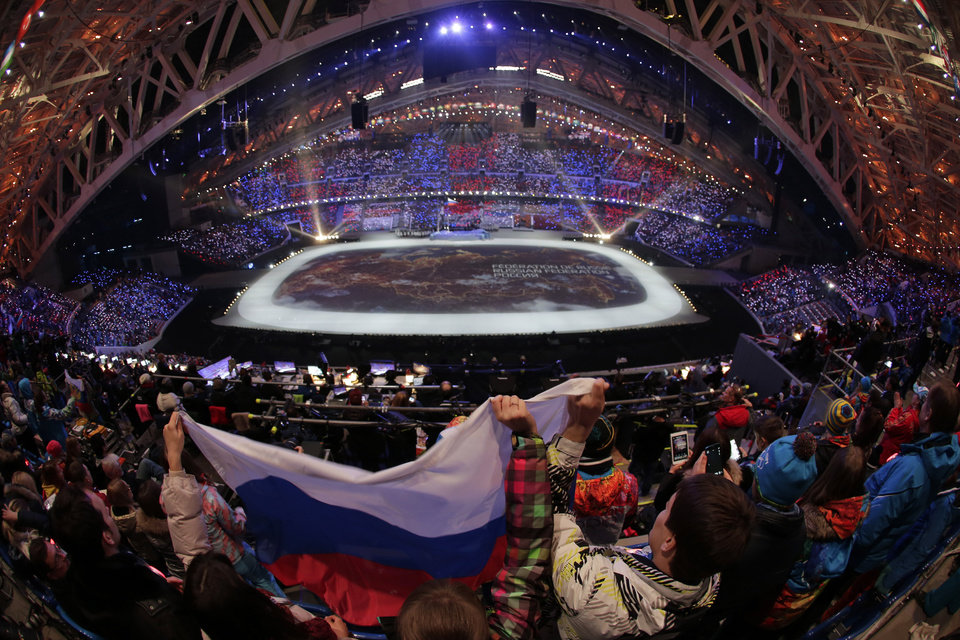 Photo - Spectators wave the Russian flag during the opening ceremony of the 2014 Winter Olympics in Sochi, Russia, Friday, Feb. 7, 2014. (AP Photo/Charlie Riedel)