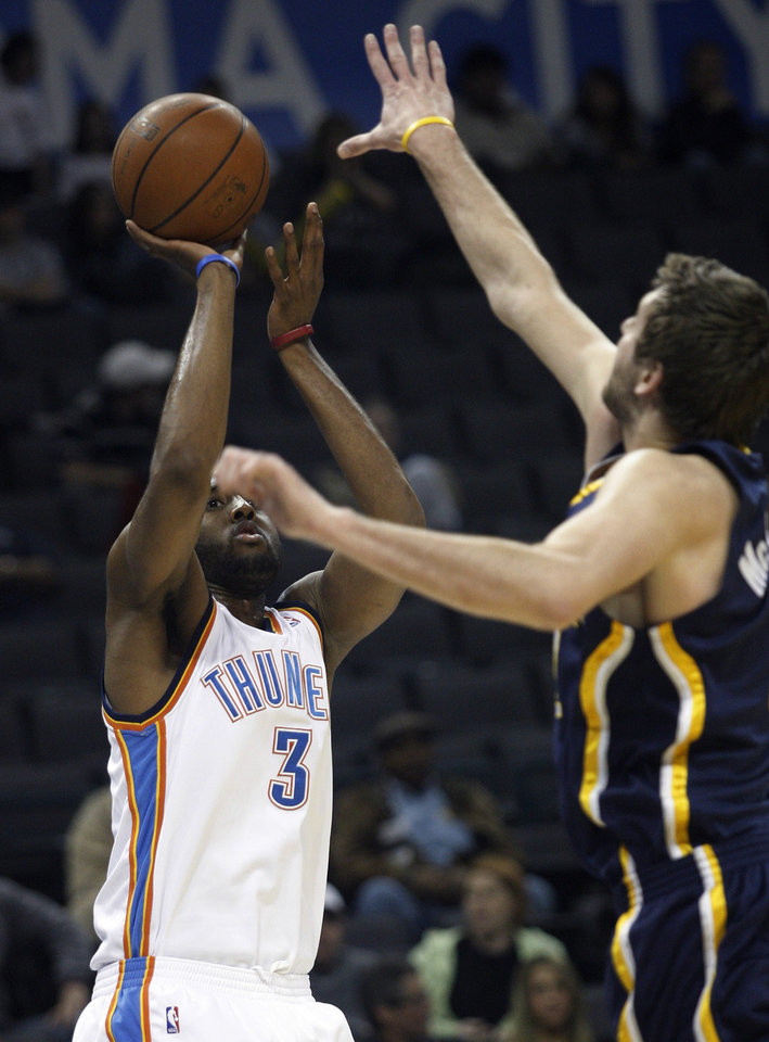 Photo - Oklahoma City Thunder forward D.J. White, left, takes a shot as Indiana Pacers forward Josh McRoberts defends in the first quarter of an NBA basketball game in Oklahoma City, Sunday, April 5, 2009. White scored 14 points for Oklahoma City in his NBA debut, but Indiana won 117-99. (AP Photo/Sue Ogrocki) ORG XMIT: OKSO113