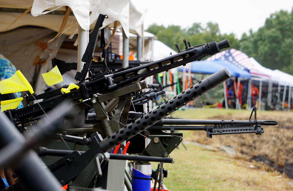 Photo - A line of machine guns is seen Saturday at the Oklahoma Full Auto Shoot and Trade Show Saturday in Wyandotte. [Jordan Green/The Oklahoman]
