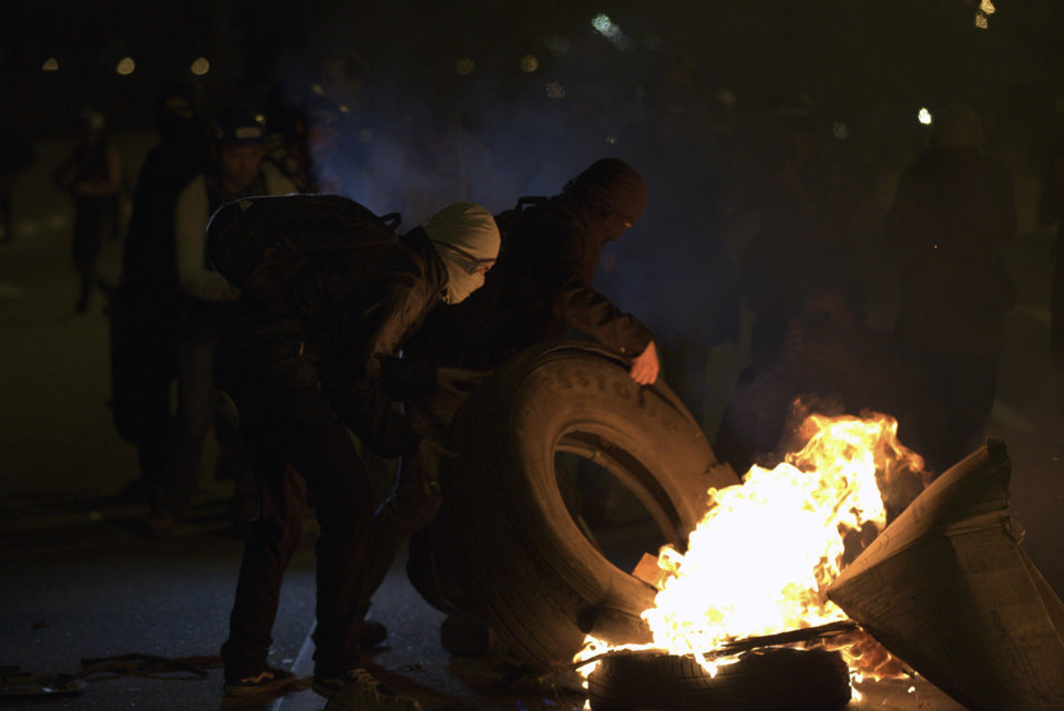 Photo - Masked demonstrators burn tires after a march in Sao Paulo, Brazil, Thursday, June 19, 2014. The protest in Sao Paulo, Brazil's biggest city that is hosting a World Cup match, was called by the Free Fare movement, the group that was behind the first protests last year that sparked roiling anti-government demonstrations across Brazil. (AP Photo/Eduardo Verdugo)