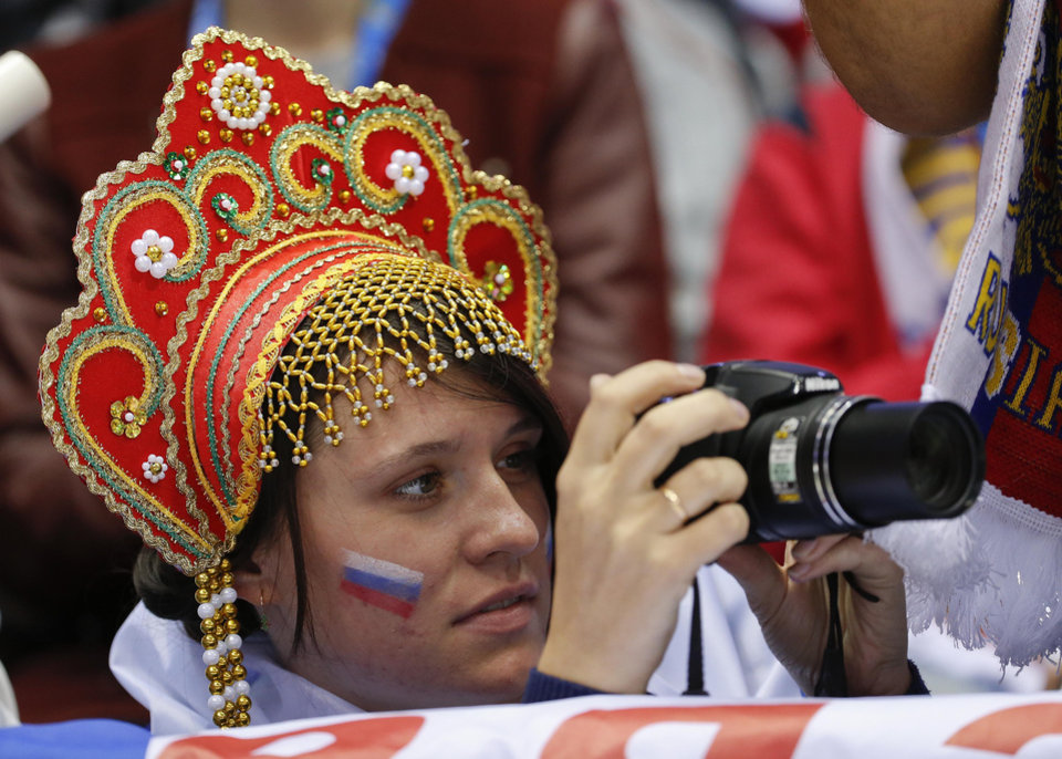 Photo - A hockey fan rooting for Russia takes photos during the second period of a men's ice hockey game against Slovenia at the 2014 Winter Olympics, Thursday, Feb. 13, 2014, in Sochi, Russia. (AP Photo/Julio Cortez)