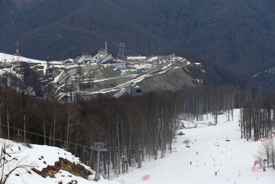Photo - A view from near the alpine course showing the difference between the snow covered piste and the snowless lower slopes at the Sochi 2014 Winter Olympics, Tuesday, Feb. 11, 2014, in Krasnaya Polyana, Russia. Warm temperatures in the mountains made the snow too soft and caused the cancellation of women's downhill training on Tuesday.  (AP Photo/Luca Bruno)