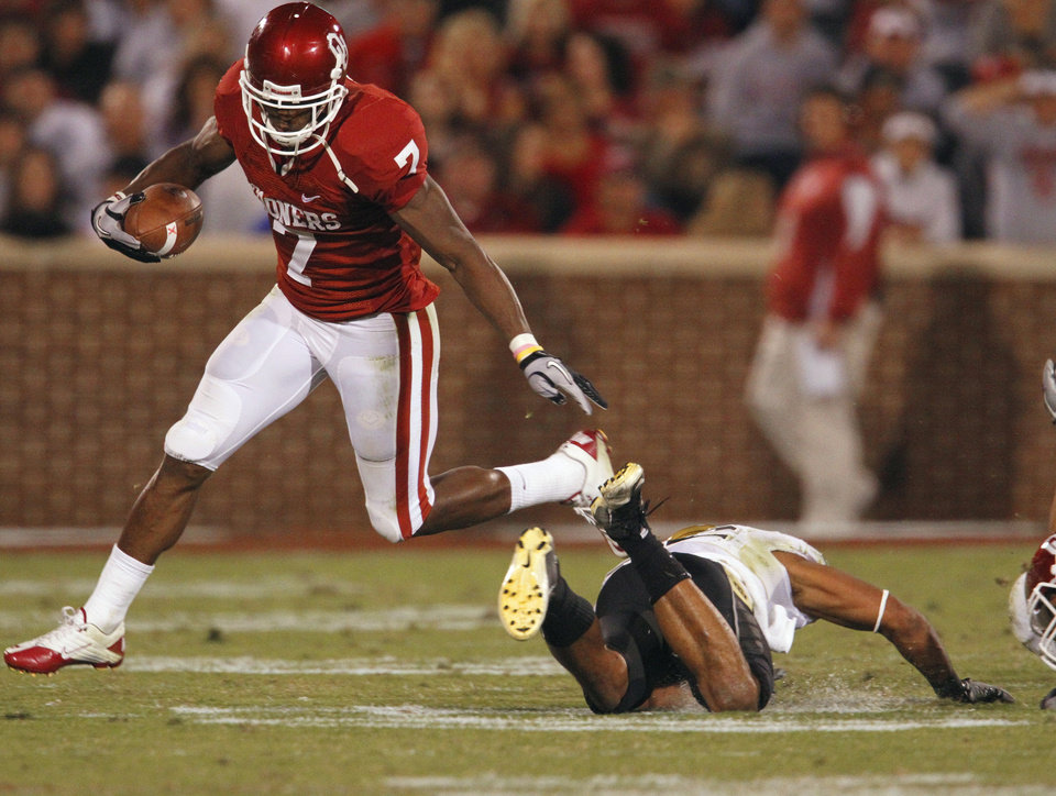 Photo - DeMarco Murray (7) carries during the first half of the college football game between the University of Oklahoma (OU) Sooners and the University of Colorado Buffaloes at Gaylord Family-Oklahoma Memorial Stadium in Norman, Okla., Saturday, October 30, 2010.  Photo by Steve Sisney, The Oklahoman
