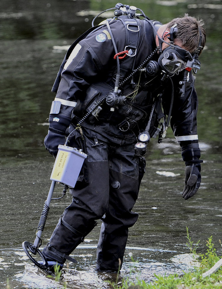 Photo - A member of the Connecticut State Police Dive Team searches with a metal detector at Pine Lake in Bristol, Conn., the hometown of the former New England Patriots player Aaron Hernandez,  Monday, July 29, 2013. Hernandez has pleaded not guilty to murder in the death of Odin Lloyd, a 27-year-old Boston semi-professional football player. (AP Photo/Jessica Hill)