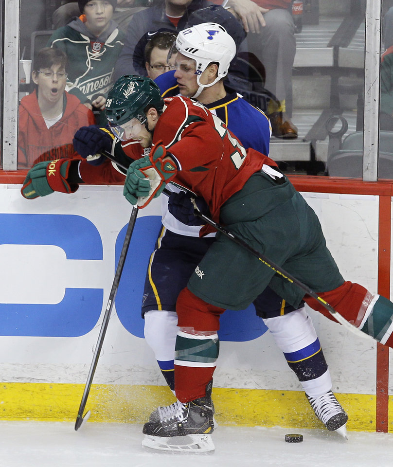 Photo - Minnesota Wild defenseman Nate Prosser, front, checks St. Louis Blues center Vladimir Sobotka, of the Czech Republic, off the puck and into the boards during the first period of an NHL hockey game in St. Paul, Minn., Thursday, April 10, 2014. (AP Photo/Ann Heisenfelt)