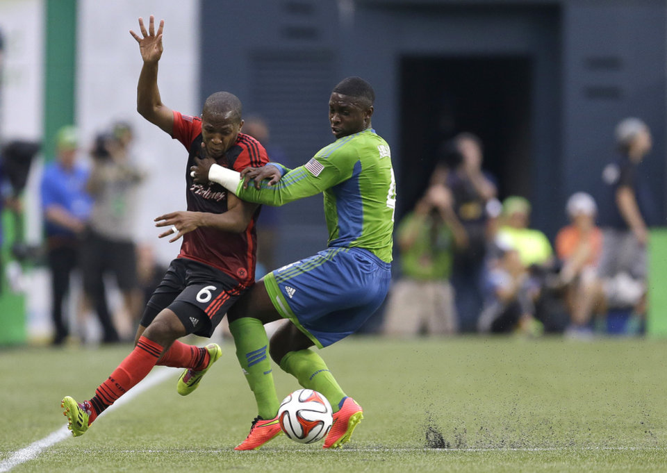 Photo - Portland Timbers' Darlington Nagbe (6) and Seattle Sounders' Jalil Anibaba, right, battle for the ball near the sideline in the first half of an MLS soccer match, Sunday, July 13, 2014, in Seattle. (AP Photo/Ted S. Warren)