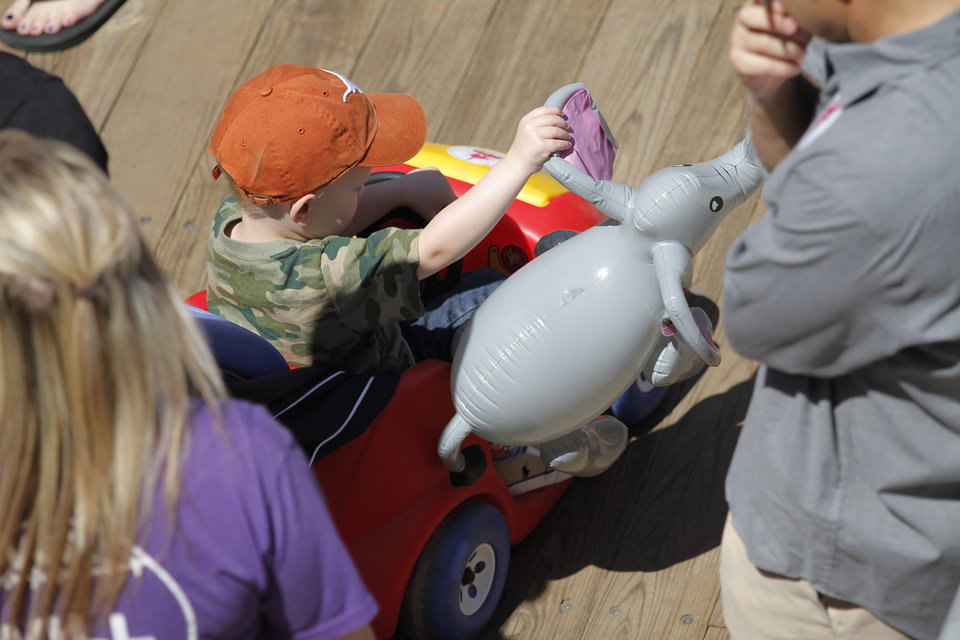 Photo - A child carries an inflatable elephant during Malee's first birthday celebration at the Oklahoma City Zoo, Sunday, April 15, 2012.  Photo by Garett Fisbeck, For The Oklahoman