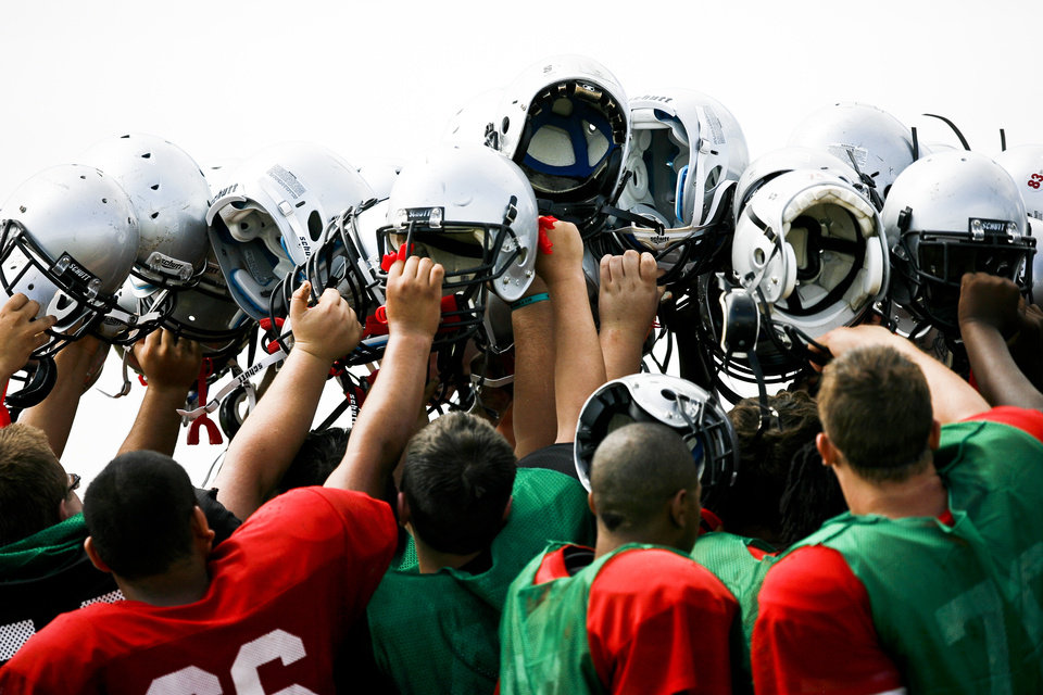 Photo - Generals players hold their helmets up after a scrimmage at U.S. Grant High School on Saturday, Aug. 13, 2011. Photo by Zach Gray, The Oklahoman