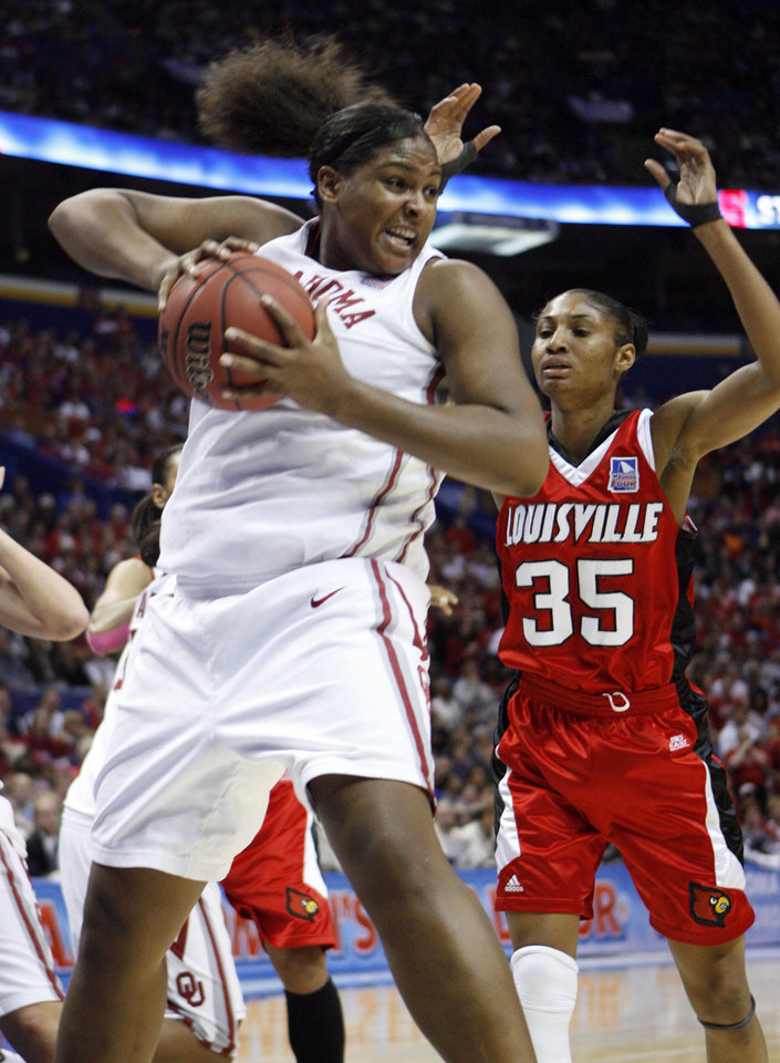 Photo - Courtney Paris pulls in a rebound in front of Angel McCoughtry in the first half as the University of Oklahoma plays Louisville at the 2009 NCAA women's basketball tournament Final Four in the Scottrade Center in Saint Louis, Missouri on Sunday, April 5, 2009. Photo by Steve Sisney, The Oklahoman