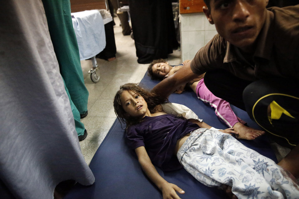 Photo - Palestinian children, wounded in an Israeli strike on a compound housing a U.N. school in Beit Hanoun, in the northern Gaza Strip, lay on the floor of an emergency room at the Kamal Adwan hospital in Beit Lahiya, Thursday, July 24, 2014. Israeli tank shells hit the compound, killing more than a dozen people and wounding dozens more who were seeking shelter from fierce clashes on the streets outside. Gaza health official Ashraf al-Kidra says the dead and injured in the school compound were among hundreds of people seeking shelter from heavy fighting in the area. (AP Photo/Lefteris Pitarakis)