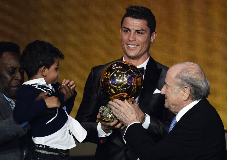 Photo - Cristiano Ronaldo of Portugal, center, is awarded the prize for the FIFA Men's soccer player of the year 2013 by FIFA President Sepp Blatter, right, at the FIFA Ballon d'Or 2013 gala at the Kongresshaus in Zurich, Switzerland, Monday, Jan. 13, 2014. (AP Photo, Keystone/Steffen Schmidt)
