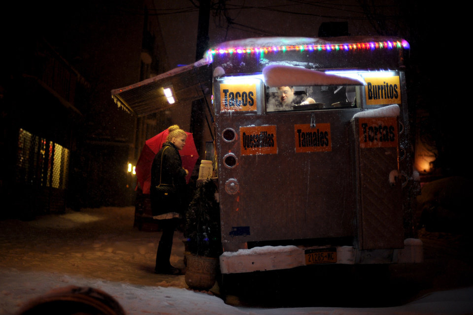 Photo - Asrael Velazquez, right, prepares an order for Amelie, who declined to provide her last name, of Germany, at the Casa Mexicana food cart early Saturday, Feb. 9, 2013, in the Williamsburg section of the Brooklyn borough of New York. Snow began falling across the Northeast on Friday, ushering in what was predicted to be a huge blizzard. (AP Photo/Jeffrey Furticella)