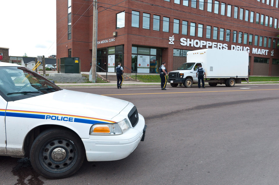 Photo - Royal Canadian Mounted Police check a van at a roadblock in Moncton, New Brunswick on Thursday, June 5, 2014. A Royal Canadian Mounted Police manhunt for a gunman suspected of killing three Mounties and wounding two others passed the 12-hour mark Thursday in Moncton as a large section of the New Brunswick city was under a virtual siege. (AP Photo/The Canadian Press, Marc Grandmaison)